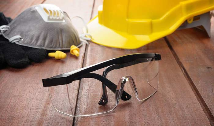 Safety gear for bridge workers, including a hard hat, goggles, earplugs and respiratory protection.