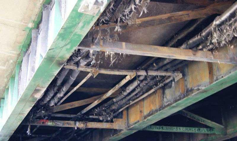 Man-caused fire damage to under-bridge utilities.