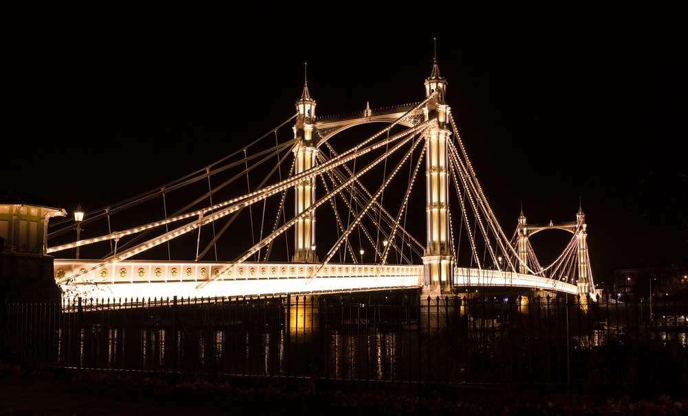 The intricate Albert Bridge illuminated at night.
